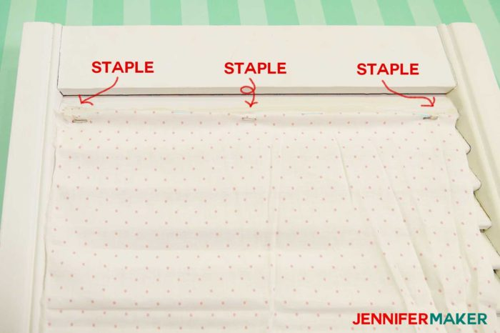 Start by stapling one end of the fabric to the bottom of the slat in three spots to make a DIY paper organizer