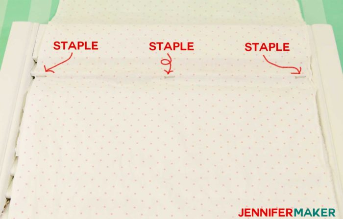 Staple the fabric to the bottom of the slat in three spots to make a DIY paper organizer