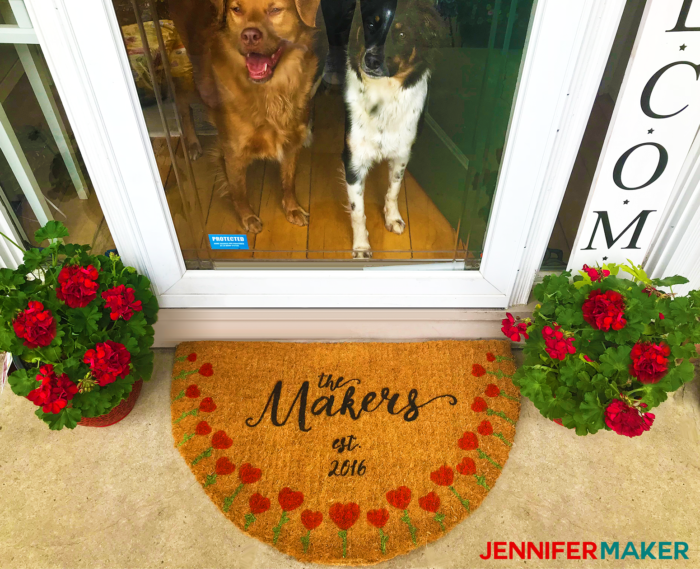 A DIY painted and personalized door mat in front of a house door with my two cute dogs