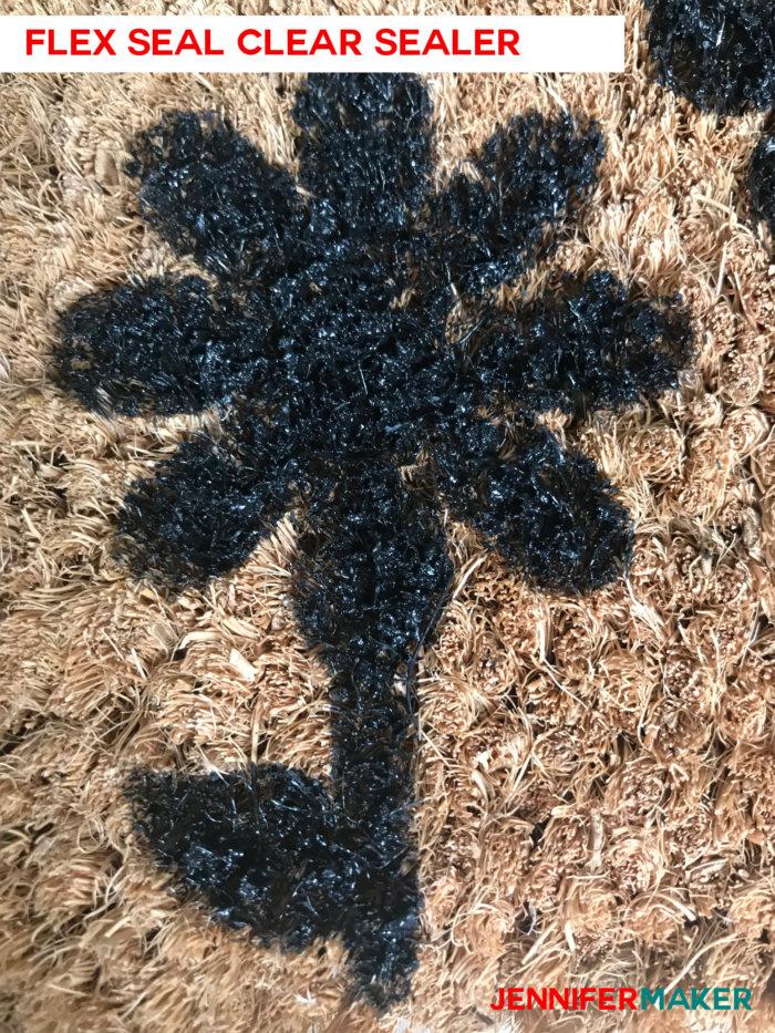 Close up of a DIY personalized door mat made of coir, painted with exterior house paint, and sealed with Flex Seal Clear Spray