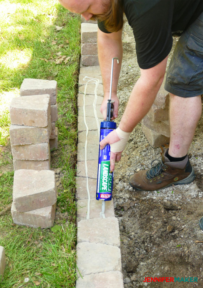 Putting construction adhesive on bricks to make a retaining wall
