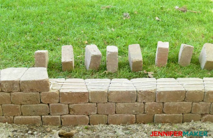 Stacking and adhesing bricks to construct a retaining wall