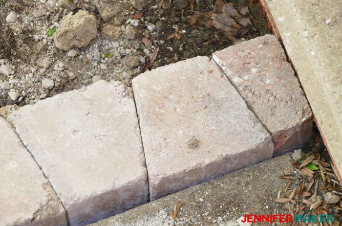 A retaining wall brick broken in half to fit into a tight spot