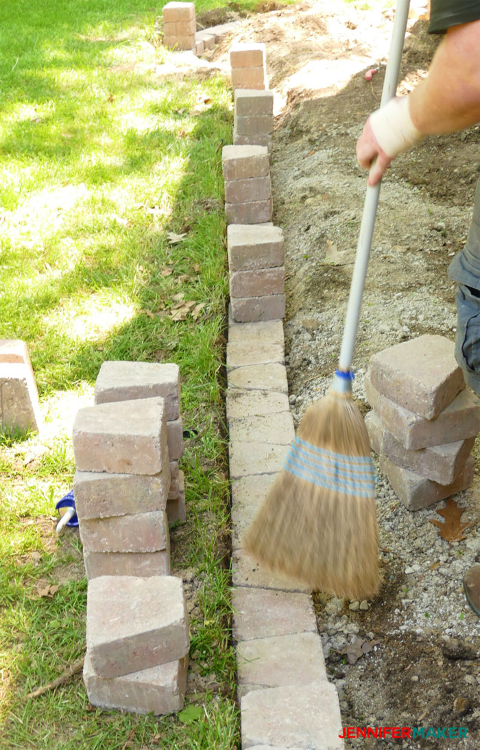 Removing dust and debris with a broom to make a retaining wall