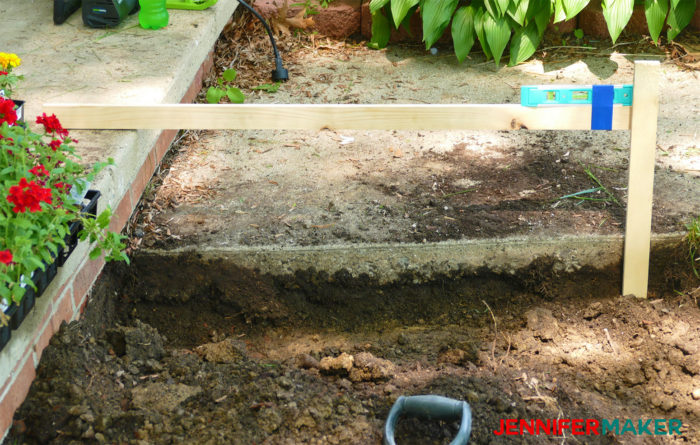 Measure the depth of a our dirt trench with a level and a stick to build DIY retaining walls