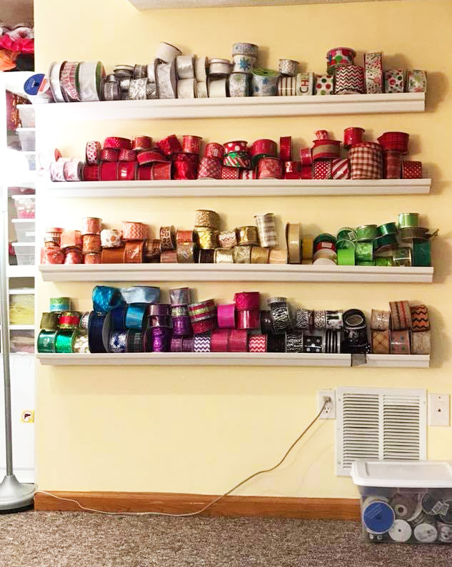 Store your ribbon spools in white rain gutters installed on a wall in a craft room for great DIY ribbon storage!