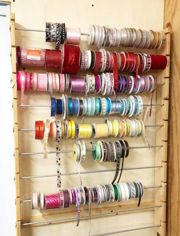 Ribbon storage rack with metal rods and wood frame