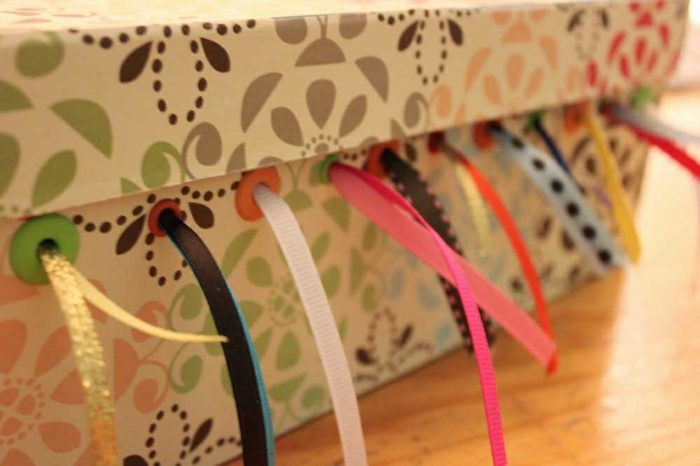 Organizer your craft ribbon in a box with holes for the ribbon to come out