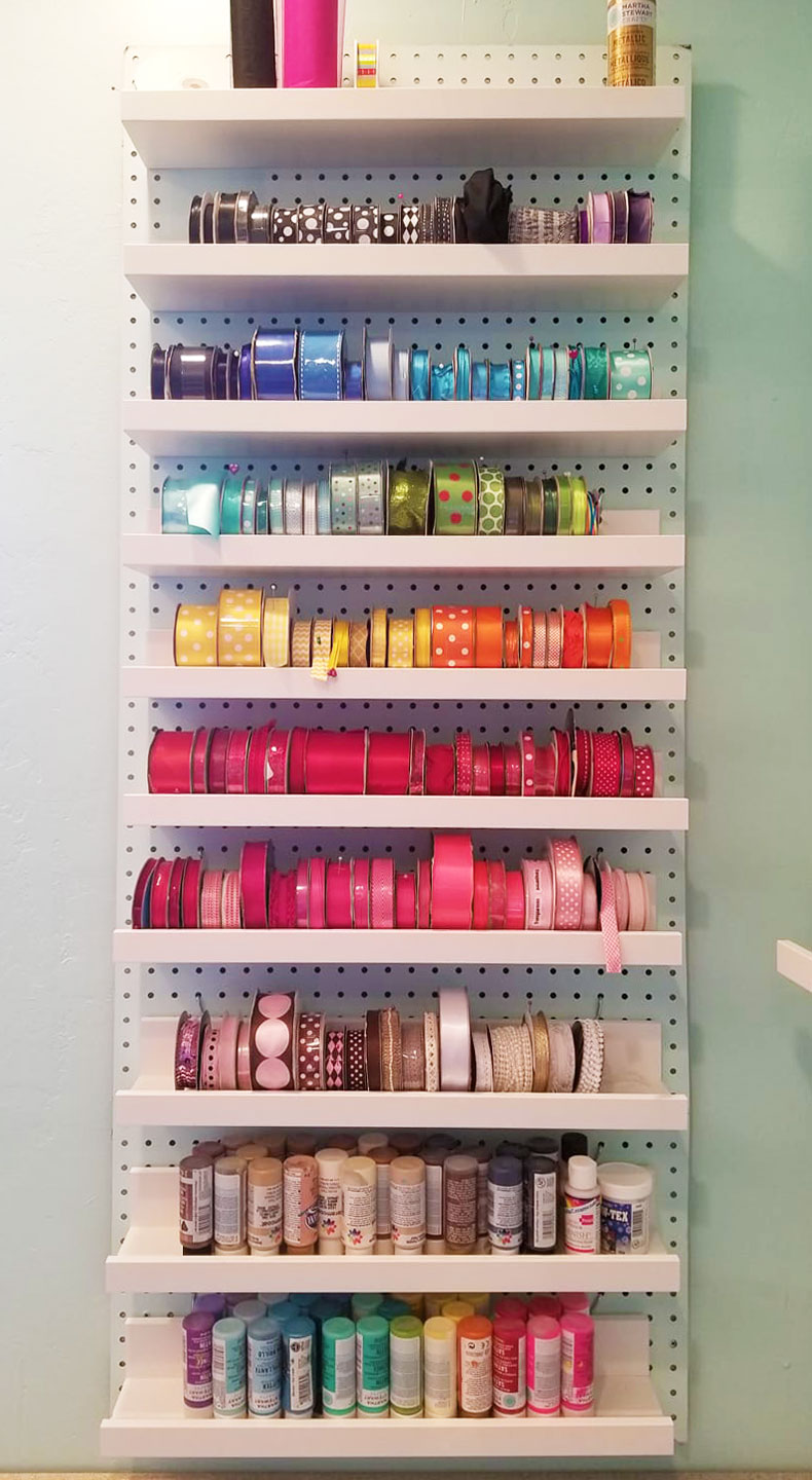 Ribbon storage on a wall: ribbon spools can be put on shelves on a pegboard to organize them! #craftroom #storage #organization