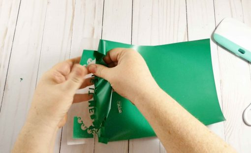 Remove the excess vinyl from the plastic backing for your diy Santa Sack design