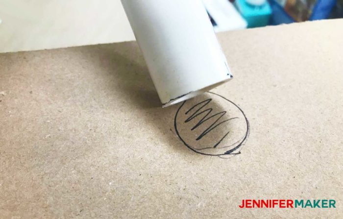 Marking the PVC pipe on the cardboard box to make a DIY tumbler turner