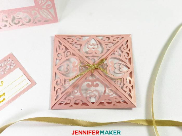 Pink laser cut filigree invitation with gold ribbon for the DIY Wedding Invitation Template Tutorial