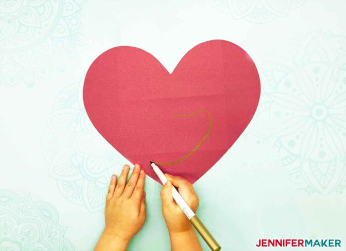 Little hands drawing a message inside the easy paper heart envelope