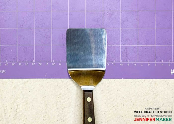 A cookie spatula on a purple Cricut StrongGrip mat