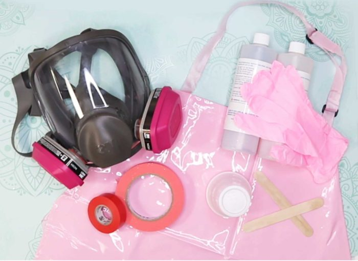 The personal protective equipment JenniferMaker uses when working with epoxy resin for her custom tumblers: respirator, nitrile gloves, PVC apron, tape, disposable cups, and more