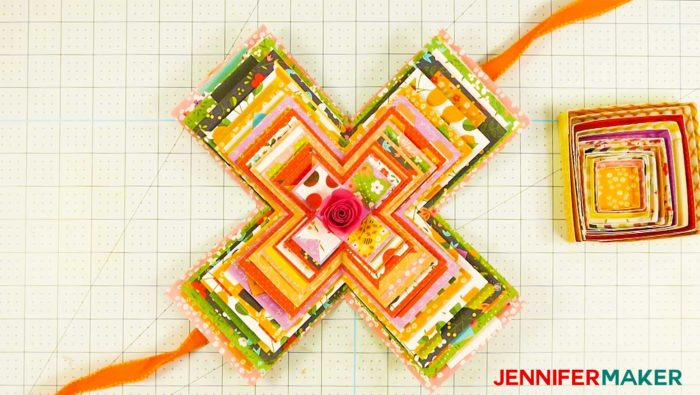 An open paper explosion box card with orange ribbon