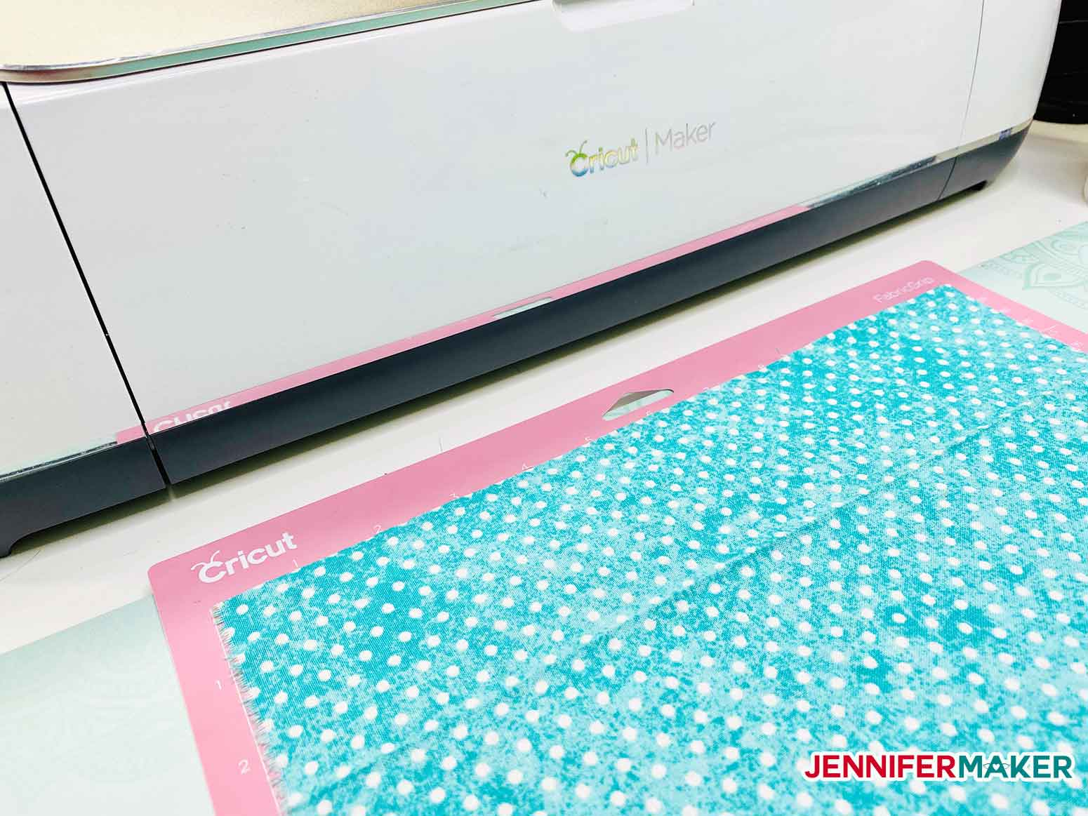 Cutting cotton on a pink FabricGrip mat with a Cricut Maker to make a no-sew face mask