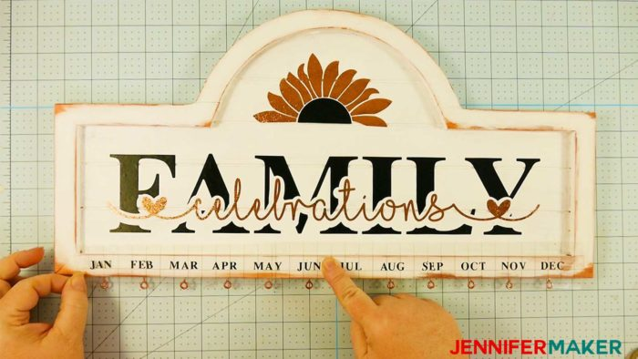Positioning black vinyl months on the bottom of a family celebration and birthday board