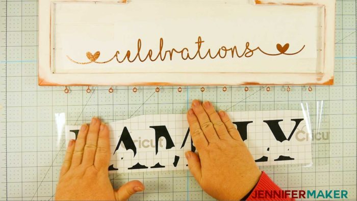 Placing transfer tape on top of a black vinyl decal to make a family celebration and birthday board