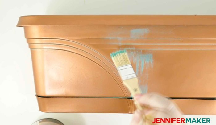 Brush on metallic paint to make a faux copper patina paint on an old plastic planter