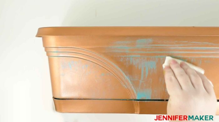 Wiping the aquamarine metallic paint off the copper to create a faux copper patina paint effect
