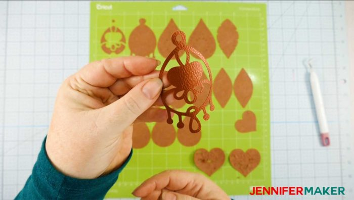 A cut faux leather earring and a Cricut cutting mat to create faux leather earrings