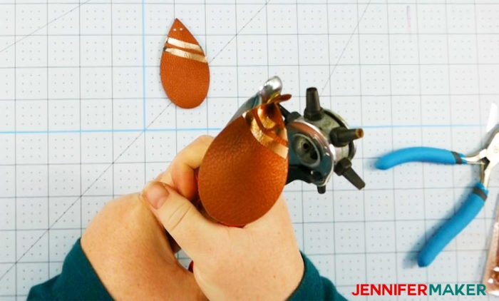 Punching faux leather with a leather punch to make the holes for faux leather earrings