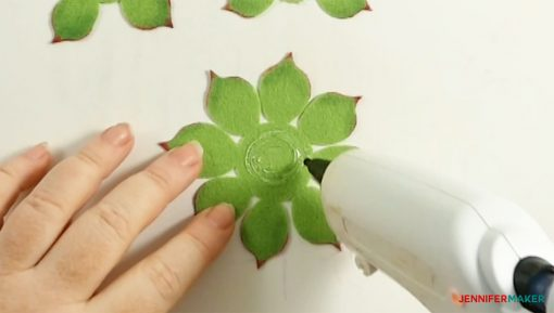 Apply hot glue in a ring in the center of your largest set of leaves