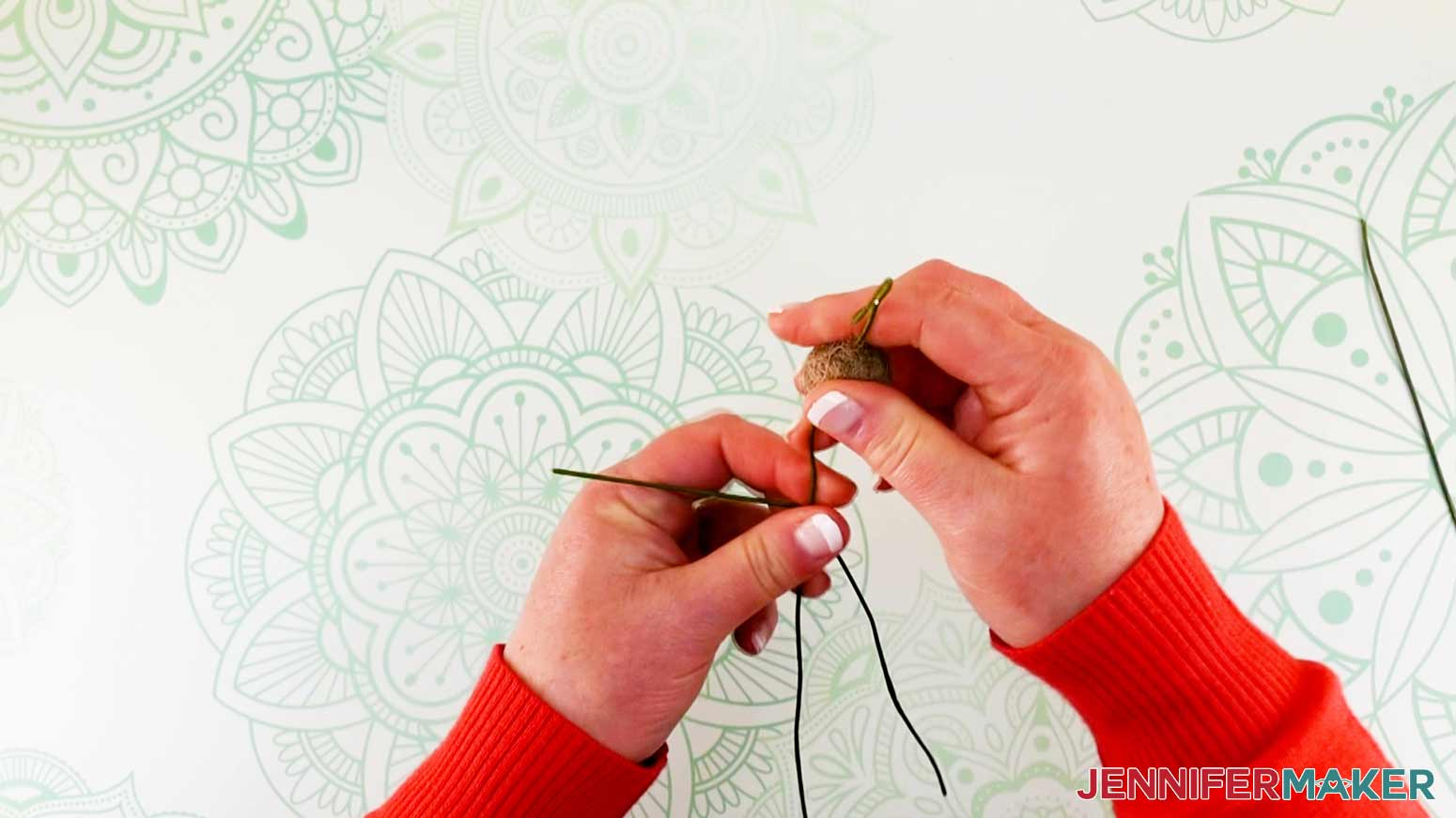 Bending arm wire of flower fairy doll around body wire and positioning leg parallel