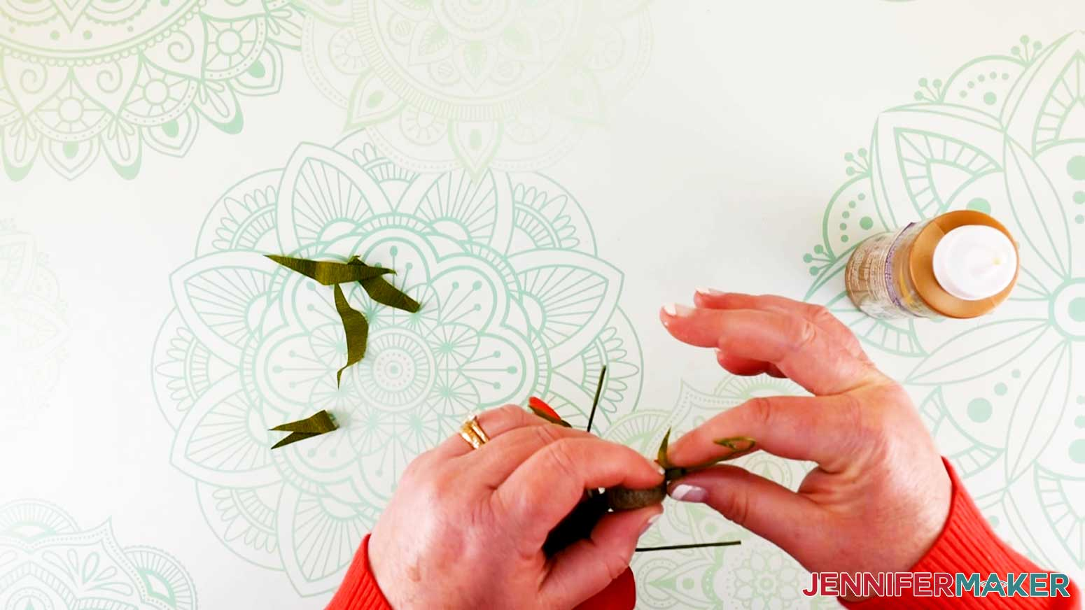 Holding head leaf in place while wrapping other end around wire of flower fairy doll