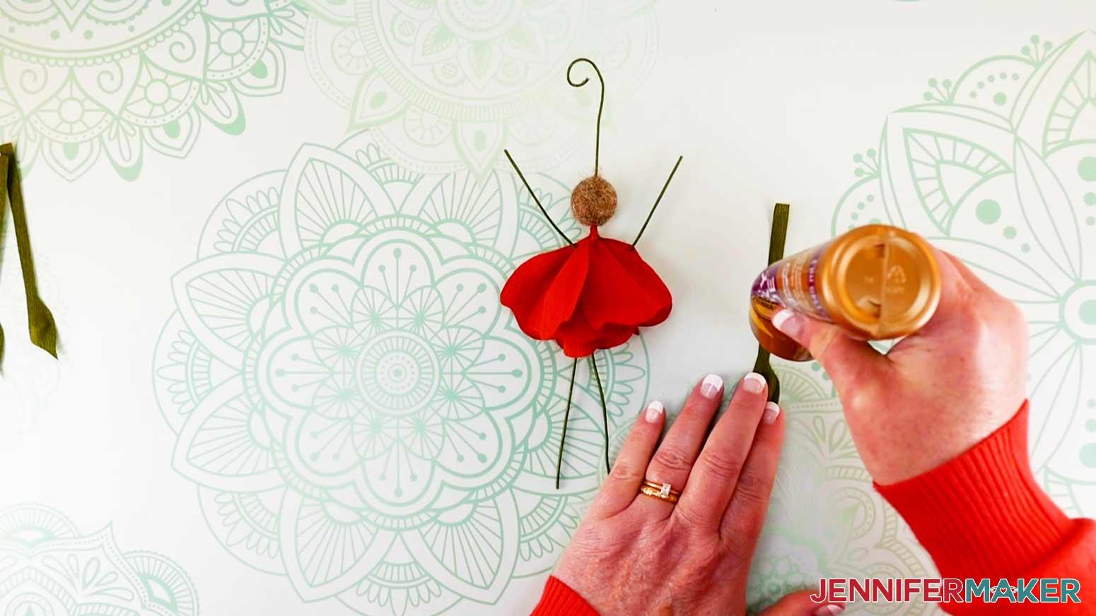 Dabbing glue onto leaf base of peony flower fairy doll