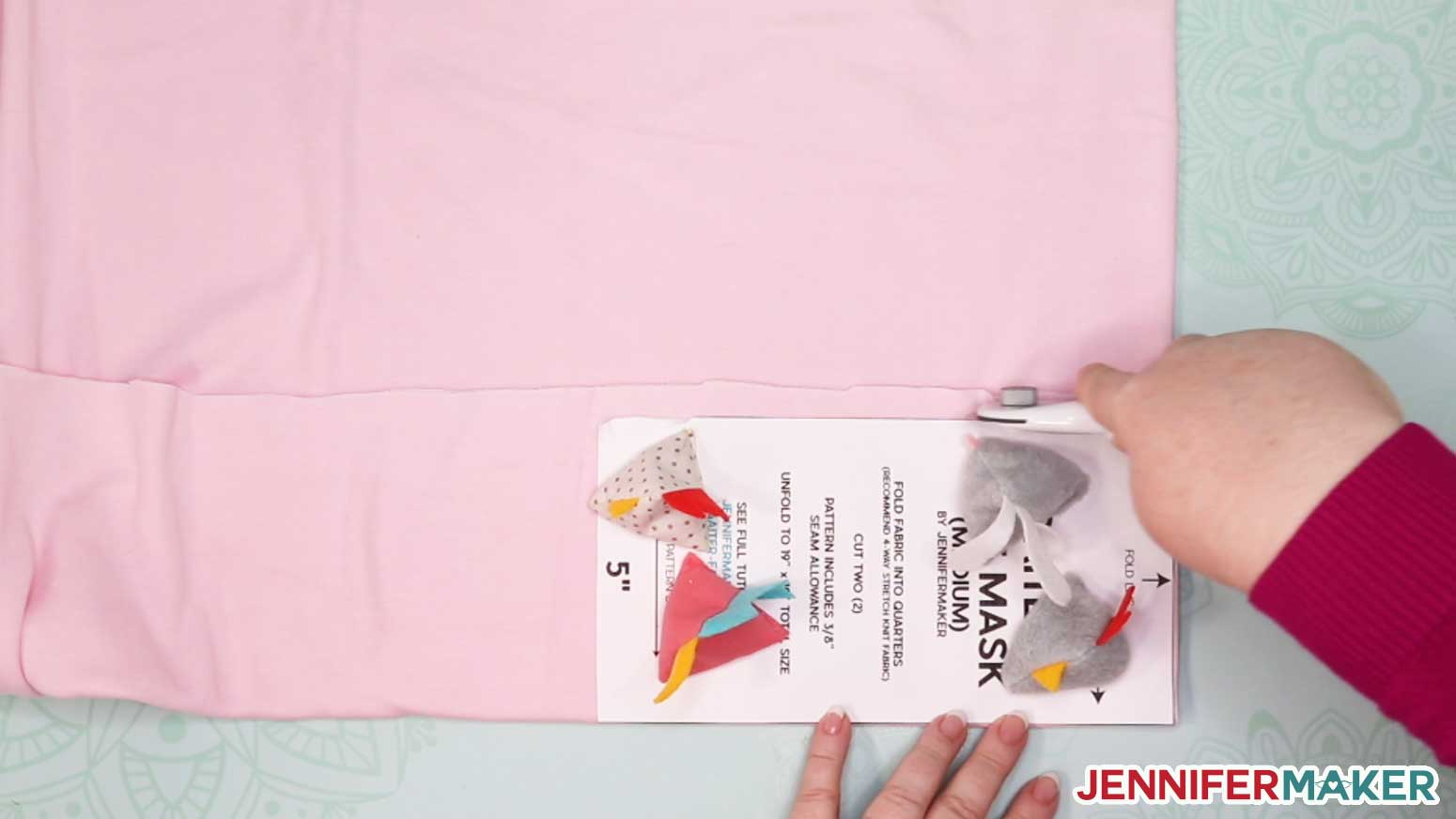 Cutting pink knit fabric with a rotary cutter to make a DIY gaiter face mask