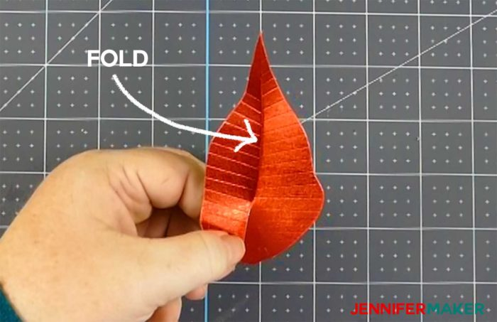 Folding a red paper poinsettia leave to make a giant paper poinsettia flower