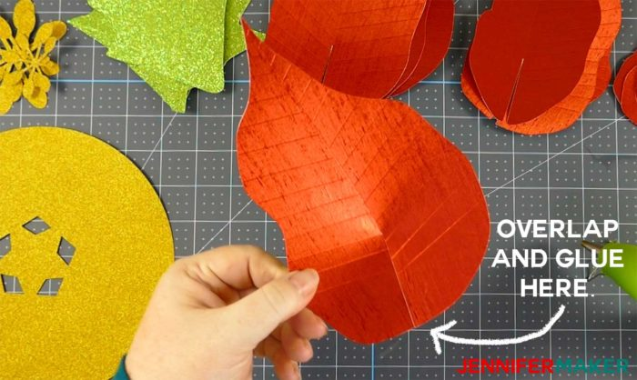 A red foil paper poinsettia leave being glued to create a giant paper poinsettia flower