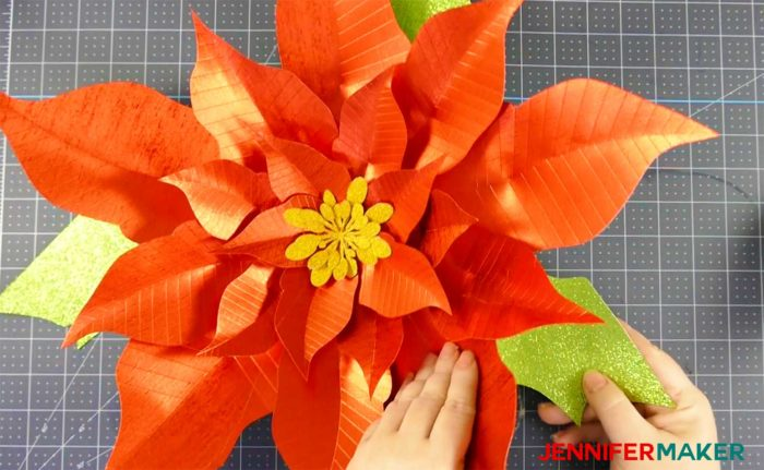 Tucking green paper leaves into the giant red paper poinsettia flower