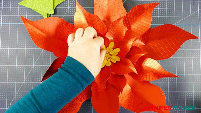 Gluing in a yellow paper poinsettia stamen to make a giant paper poinsettia flower
