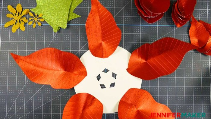 Five paper poinsettia leaves arranged in a star pattern to form a giant paper poinsettia flower
