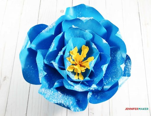 Glitter and snow on the giant paper winter rose in blue and yellow
