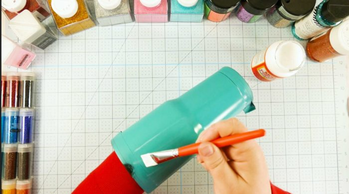 Brushing on Mod Podge onto a painted tumbler is step 3 of the glitter tumbler tutorial