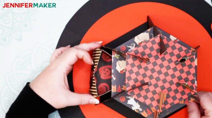 Carefully sliding a treat box into the DIY Halloween Countdown Calendar