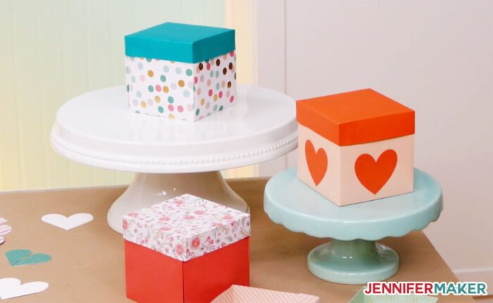 Colorful heart explosion boxes on cake plates made with the free heart explosion box template SVG cut file by JenniferMaker