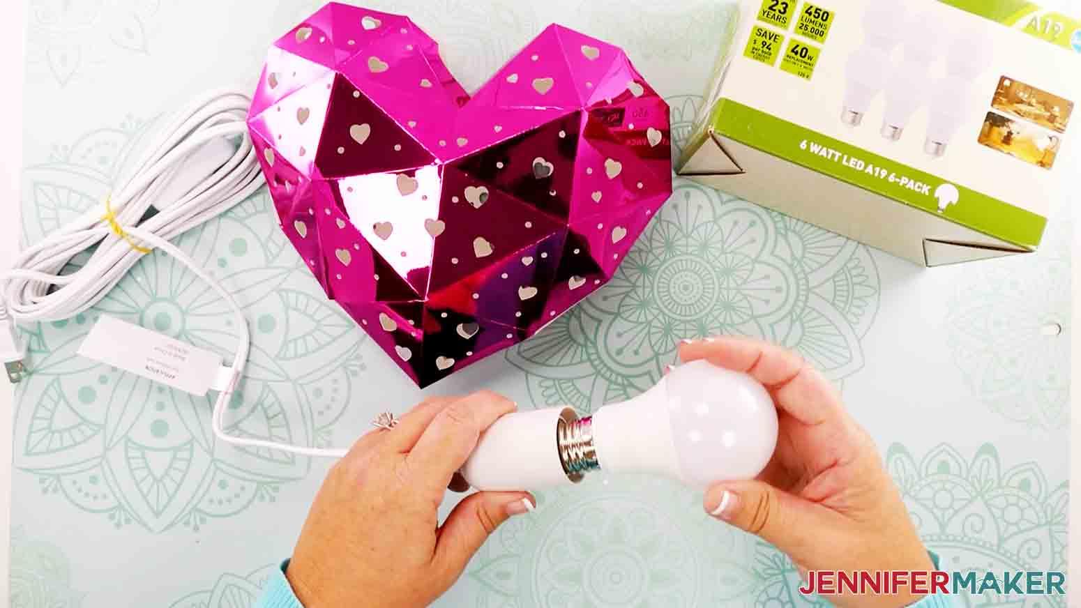 screwing in light bulb to light the heart lantern