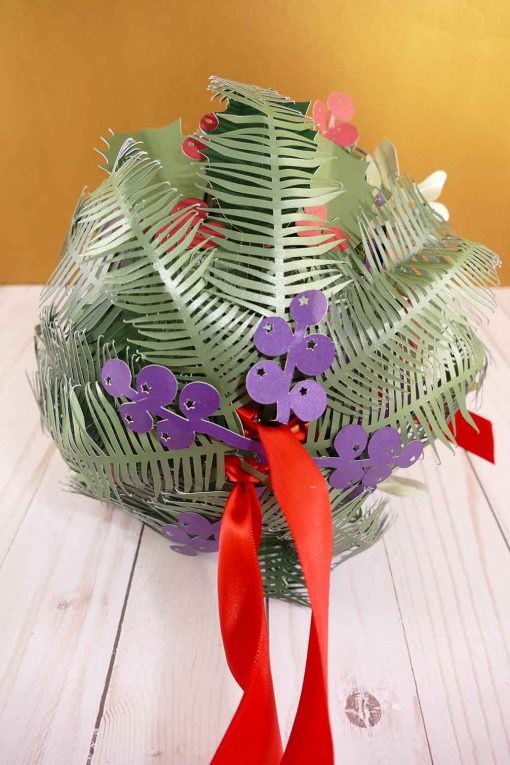 Finish up your holiday kissing ball with evergreens and juniper berries.