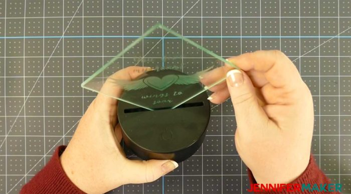 Putting hot glue in an LED light base to light up a glass etching