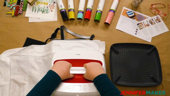 Pressing down on a layered iron on vinyl design on a black tote bag with a Cricut EasyPress 2