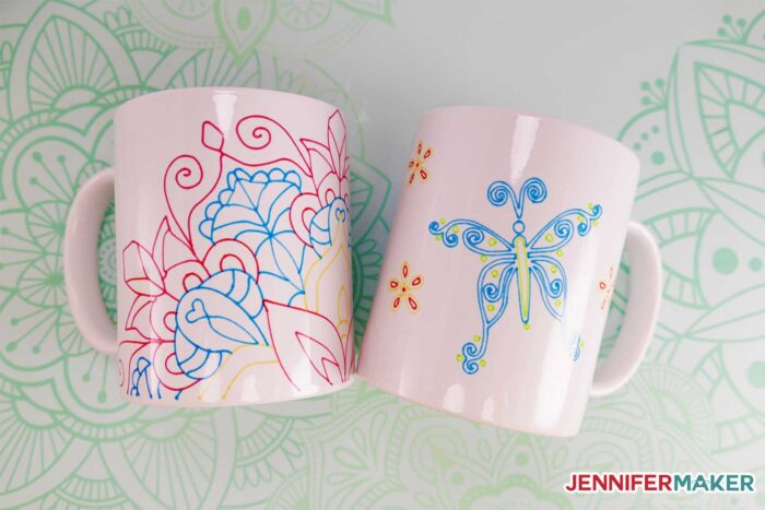 Pretty Infusible Ink pen mugs with a colorful mandala and blue and green butterfly, both made with the Cricut Mug Press