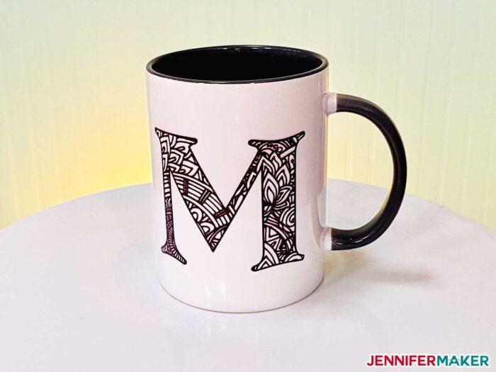Mandala monogram mug made with a black Infusible Ink pen and the Cricut Mug Press