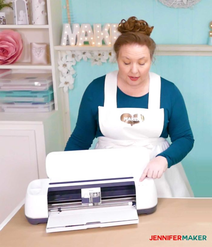 Jennifer Maker standing in front of her Cricut maker and showing how to make something