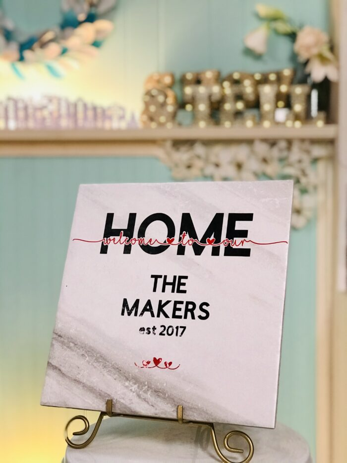 A pretty Welcome to Our Home sign on a ceramic tile made with the knockout design technique in Cricut Design Space