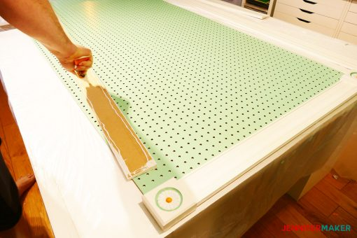 Gluing the moulding to the large pegboard to make a frame